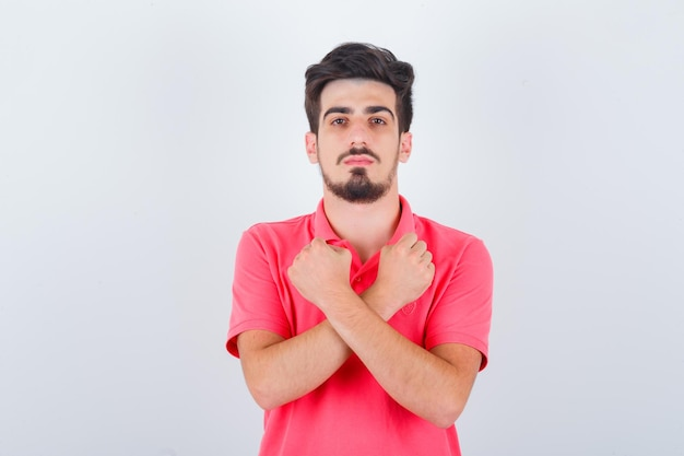 Młody mężczyzna trzyma skrzyżowane pięści na klatce piersiowej w t-shirt i wygląda pewnie, widok z przodu.