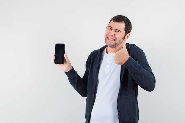 Młody mężczyzna trzyma smartfon, pokazując kciuk w białej koszulce i czarnej bluzie z kapturem na zamek błyskawiczny i wyglądający na szczęśliwego. przedni widok.