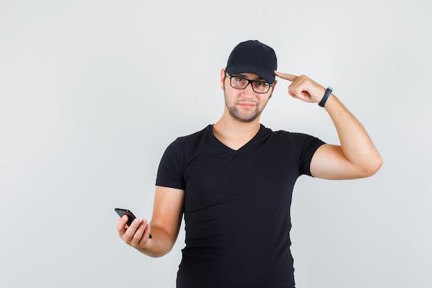 Młody mężczyzna trzyma smartfon, wskazując na głowę w czarnej koszulce