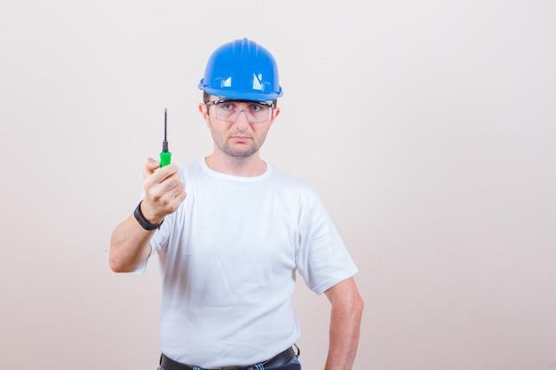 Młody mężczyzna trzyma śrubokręt w koszulce, dżinsach, kasku i wygląda poważnie