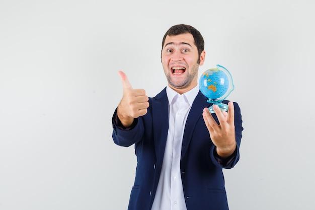 Młody mężczyzna trzyma szkolną kulę ziemską, pokazując kciuk w koszulę i kurtkę i patrząc szczęśliwy