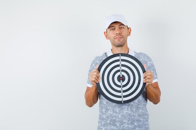 Młody mężczyzna trzyma tarczę w t-shirt i czapkę i wygląda rozsądnie