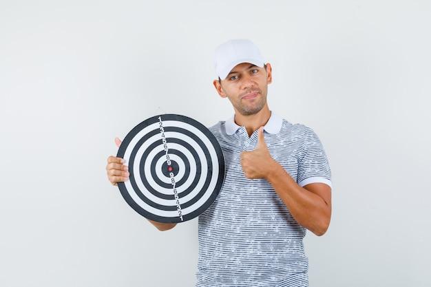 Młody mężczyzna trzyma tarczę z kciukiem w t-shirt i czapkę i wygląda zadowolony
