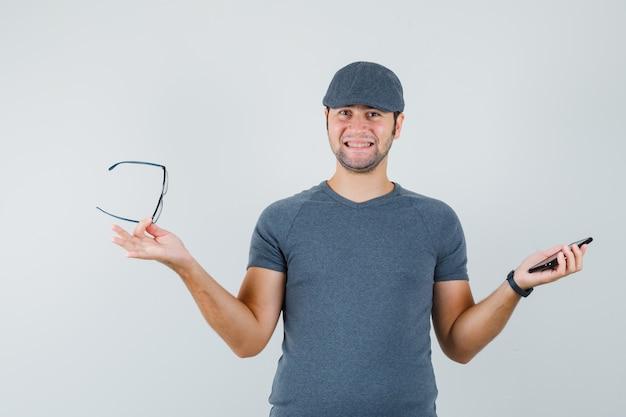 Młody mężczyzna trzyma telefon komórkowy i okulary w szarej czapce t-shirt i patrząc wesoło