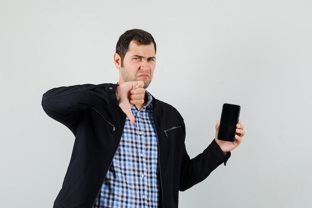 Młody mężczyzna trzyma telefon komórkowy, pokazując kciuk w dół w koszuli, kurtce i patrząc ponuro