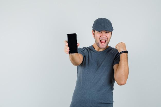 Młody mężczyzna trzyma telefon komórkowy w czapce t-shirt i patrzy błogi