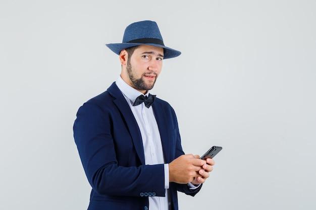 Młody mężczyzna trzyma telefon komórkowy w garniturze, kapeluszu i patrząc pewnie, z przodu.