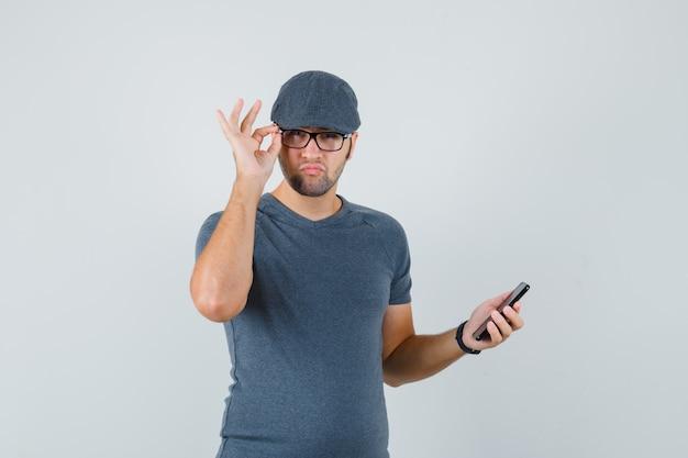 Młody mężczyzna trzyma telefon komórkowy w szarej czapce t-shirt i wygląda wątpliwie