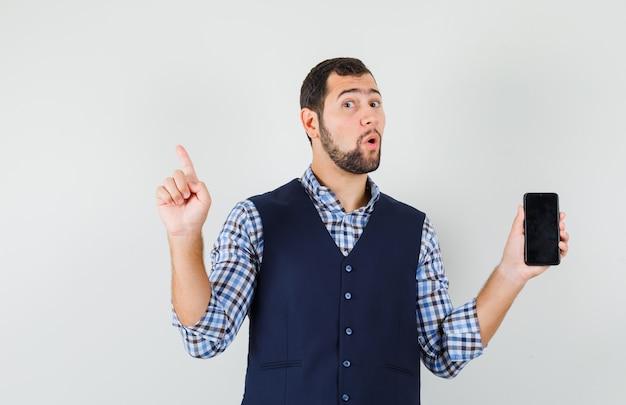 Młody mężczyzna trzyma telefon komórkowy, wskazując w koszuli