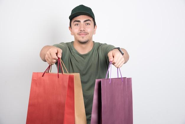 Młody mężczyzna trzyma torby na zakupy na białym tle.