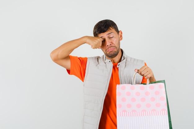 Młody mężczyzna trzyma torby na zakupy, przeciera oko w t-shirt, marynarkę i wygląda smutno. przedni widok.