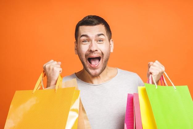 Młody mężczyzna trzyma torby na zakupy