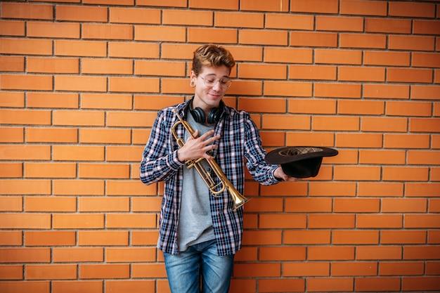 Młody mężczyzna trzyma trąbkę i skórzany kapelusz, oczekując wskazówek.