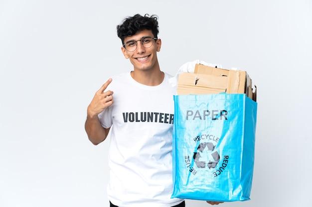 Młody mężczyzna trzyma worek recyklingu pełen papieru, dając kciuki do góry gestu