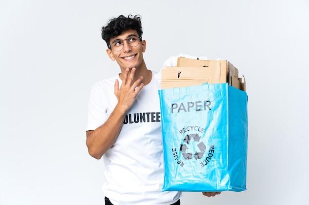 Młody mężczyzna trzyma worek recyklingu pełnego papieru, patrząc w górę, uśmiechając się