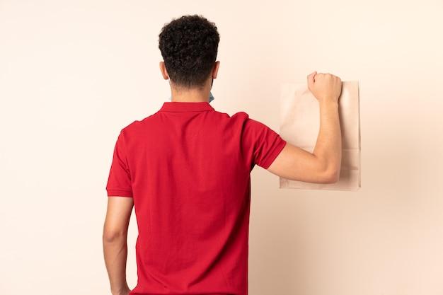 Młody mężczyzna trzyma worek żywności na wynos w tylnym położeniu