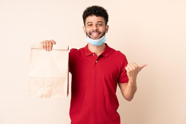 Młody mężczyzna trzyma worek żywności na wynos, wskazując w bok, aby przedstawić produkt