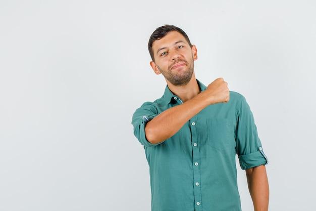 Młody mężczyzna trzyma zaciśniętą pięść w koszuli i wygląda pewnie
