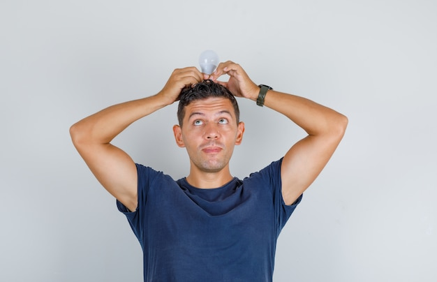 Młody mężczyzna trzyma żarówkę na głowie w granatowej koszulce i wygląda śmiesznie, widok z przodu.