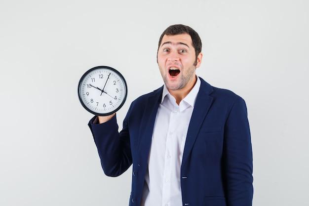 Młody mężczyzna trzyma zegar ścienny w koszuli i kurtce i wygląda zdziwiony