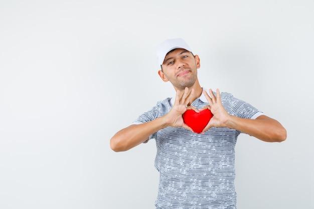 Młody mężczyzna, trzymając czerwone serce w koszulce i czapce i patrząc wesoło