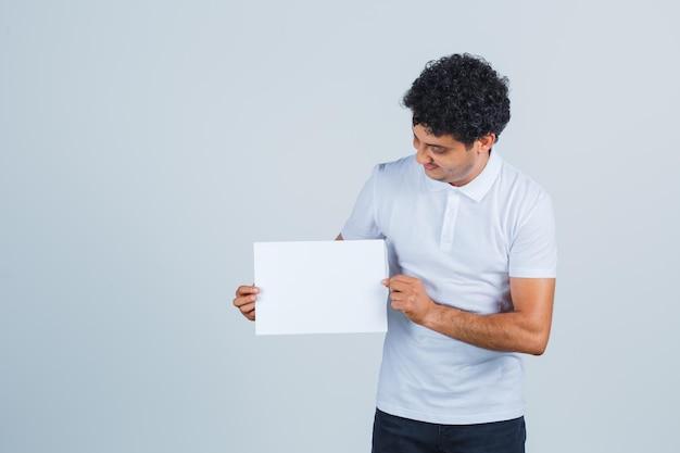 Młody mężczyzna trzymając czysty arkusz papieru w białej koszulce, spodniach i patrząc pewnie, widok z przodu.