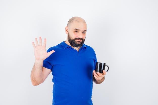 Młody mężczyzna trzymając kubek podczas machania ręką na powitanie w niebieskiej koszuli, widok z przodu.