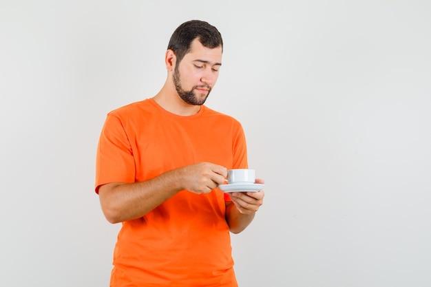Młody mężczyzna trzymając kubek ze spodkiem w pomarańczowym t-shirt i patrząc ostrożnie. przedni widok.