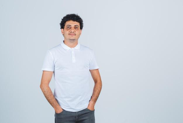 Młody mężczyzna trzymając ręce w pasie w białej koszulce, spodniach i wyglądający pewnie. przedni widok.