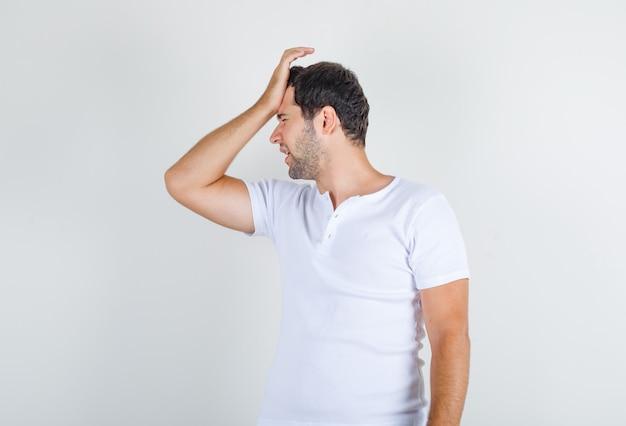 Młody mężczyzna, trzymając rękę na czole w białej koszulce i patrząc z żalem