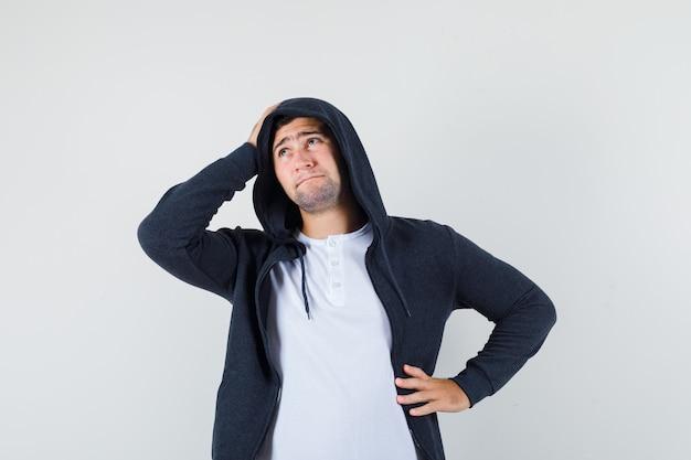 Młody mężczyzna trzymając rękę na głowie w t-shirt, kurtkę i patrząc bezradny, widok z przodu.
