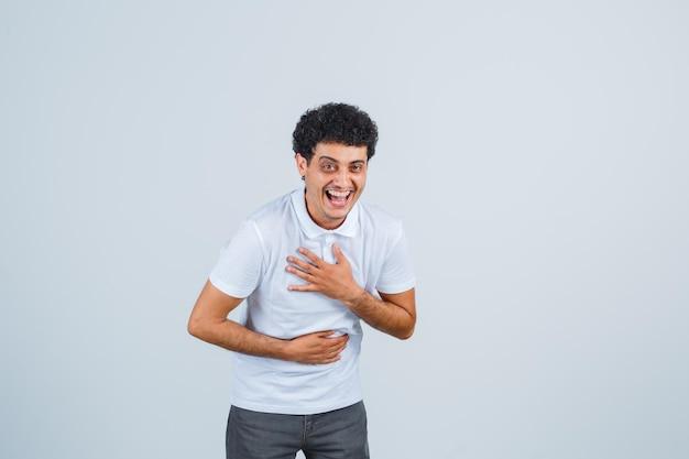 Młody mężczyzna trzymając rękę na klatce piersiowej w biały t-shirt, spodnie i patrząc szczęśliwy, widok z przodu.