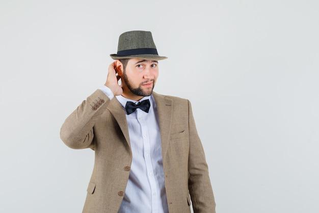 Młody mężczyzna, trzymając rękę na szyi w garniturze, kapeluszu i patrząc elegancko, widok z przodu.