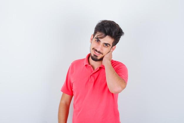 Młody mężczyzna trzymając rękę na szyi w t-shirt i patrząc szczęśliwy, widok z przodu.