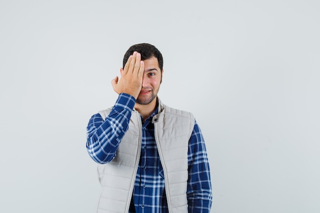 Młody mężczyzna trzymając rękę na twarzy w koszuli, kurtce bez rękawów i patrząc radośnie. przedni widok.