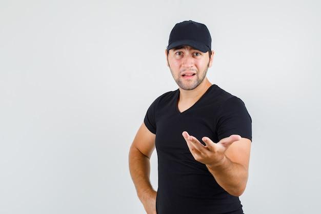 Młody mężczyzna, trzymając rękę w pytającym geście w czarnej koszulce