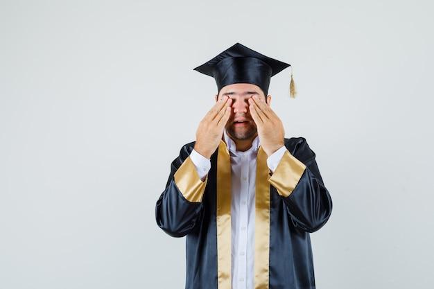 Młody mężczyzna trzymając się za ręce na oczach w mundurze absolwenta i patrząc podekscytowany. przedni widok.