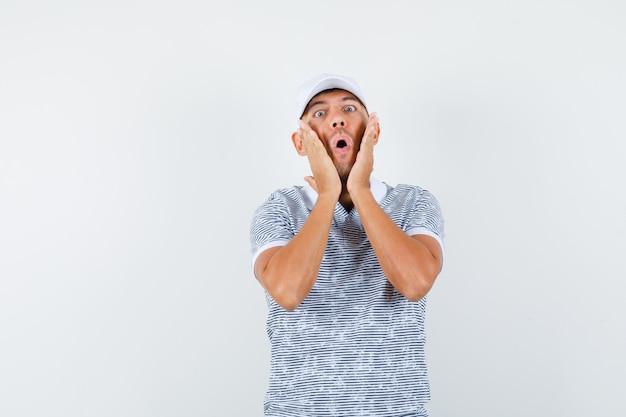 Młody mężczyzna trzymając się za ręce na policzkach w koszulce i czapce i patrząc zszokowany