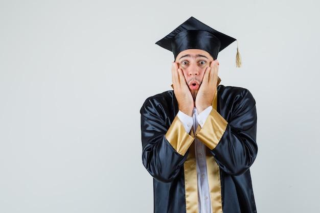 Młody mężczyzna, trzymając się za ręce na policzkach w mundurze absolwenta i patrząc niespokojnie, widok z przodu.