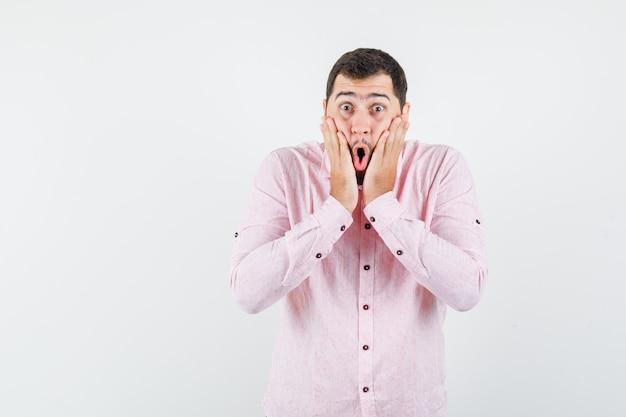 Młody mężczyzna, trzymając się za ręce na policzkach w różowej koszuli i patrząc zszokowany