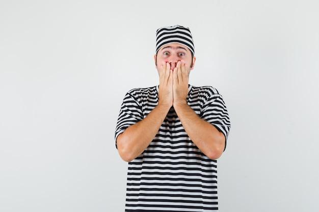 Młody mężczyzna trzymając się za ręce na ustach w t-shirt, kapelusz i patrząc przestraszony, widok z przodu.