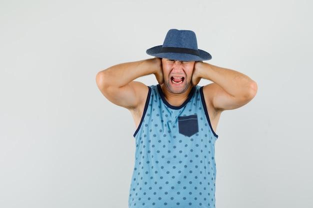 Młody mężczyzna, trzymając się za ręce na uszach w niebieskim podkoszulku, kapeluszu i poirytowany