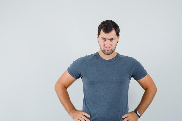 Młody mężczyzna trzymając się za ręce w pasie w szarej koszulce i patrząc poważnie