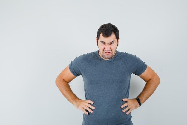 Młody mężczyzna trzymając się za ręce w pasie w szarej koszulce i patrząc wściekły