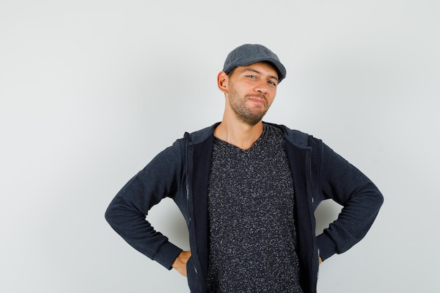 Młody mężczyzna trzymając się za ręce w talii w t-shirt, kurtkę, czapkę i patrząc wesoło, widok z przodu.