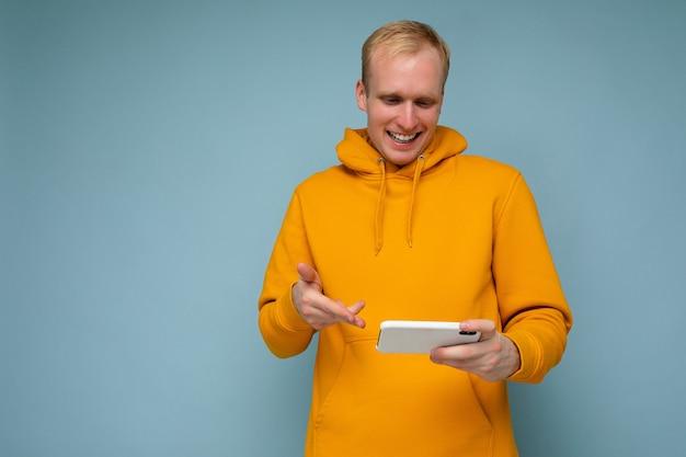 Młody mężczyzna trzymając w ręku i za pomocą telefonu komórkowego, komunikowanie się online, patrząc na ekran gadjet.
