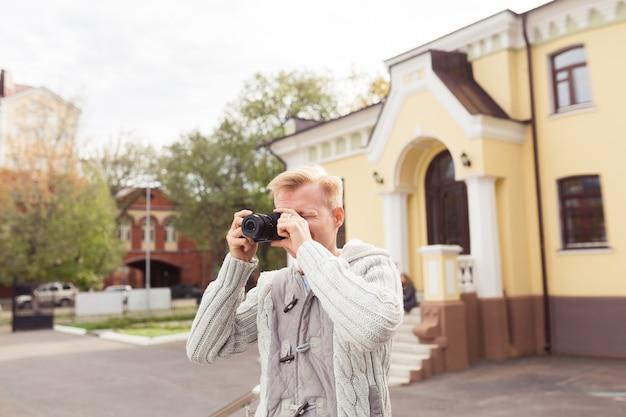 Młody mężczyzna trzymający aparat i szukający interesującego tematu do swojej sesji zdjęciowej