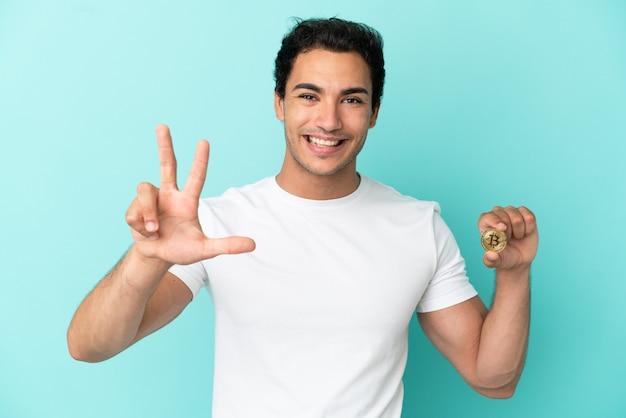Młody mężczyzna trzymający bitcoina na odosobnionym niebieskim tle szczęśliwy i liczący trzy palcami