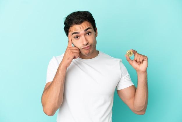 Młody mężczyzna trzymający bitcoina nad odosobnionym niebieskim tłem, myślący o pomyśle