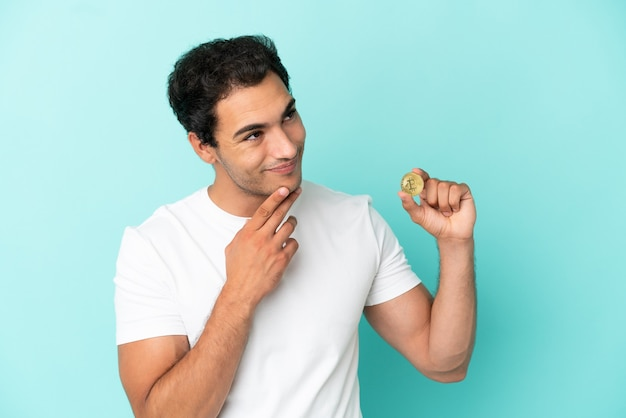 Młody mężczyzna trzymający bitcoina nad odosobnionym niebieskim tłem, patrzący w górę, uśmiechając się